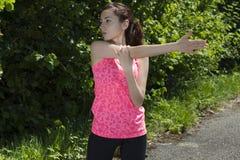 Donna adatta dei giovani che allunga il suo braccio un giorno soleggiato all'aperto nella n Immagine Stock