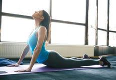 Donna adatta dei giovani che allunga sulla stuoia di yoga Immagine Stock