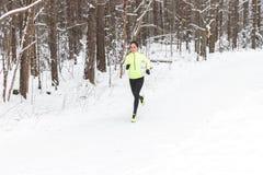 Donna adatta dei giovani che corre all'aperto in un parco il giorno di inverno freddo Immagine Stock