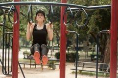 Donna adatta dei giovani che fa un allenamento di tirare su ad un campo da giuoco Immagine Stock