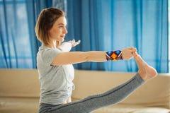 Donna adatta dei giovani che fa una posa di yoga che sta con una gamba sollevata su immagini stock libere da diritti
