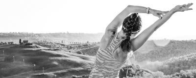 Donna adatta dei giovani contro paesaggio di allungamento della Toscana Immagine Stock