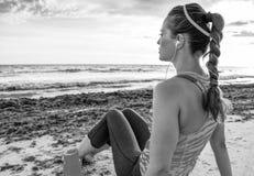 Donna adatta dei giovani pensierosi sulla spiaggia che si rilassa dopo l'allenamento Fotografie Stock Libere da Diritti