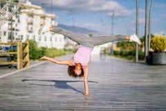 Donna adatta del nero che fa l'acrobatica di forma fisica nel fondo urbano fotografia stock libera da diritti