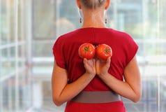 Donna adatta di affari con i pomodori come spuntino healhy - vista posteriore Fotografia Stock
