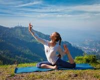 Donna adatta di Sorty che fa asana di yoga all'aperto in montagne Immagine Stock