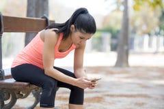 Donna adatta di sport che esamina prestazione d'inseguimento di app di Internet del telefono cellulare dopo l'allenamento corrent Fotografia Stock