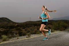 Donna adatta di sport dei giovani che corre all'aperto sulla strada asfaltata nell'allenamento di forma fisica della montagna Fotografie Stock Libere da Diritti