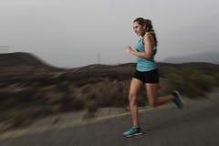 Donna adatta di sport dei giovani che corre all'aperto sulla strada asfaltata nell'allenamento di forma fisica della montagna Immagini Stock Libere da Diritti
