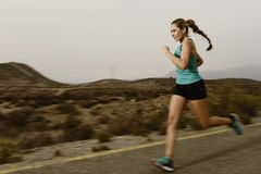 Donna adatta di sport dei giovani che corre all'aperto sulla strada asfaltata nell'allenamento di forma fisica della montagna Fotografia Stock
