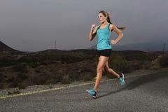 Donna adatta di sport dei giovani che corre all'aperto sulla strada asfaltata nell'allenamento di forma fisica della montagna Immagine Stock
