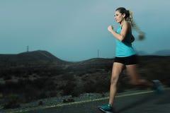 Donna adatta di sport dei giovani che corre all'aperto sulla strada asfaltata nell'allenamento di forma fisica della montagna Immagine Stock Libera da Diritti