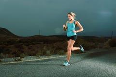 Donna adatta di sport dei giovani che corre all'aperto sulla strada asfaltata nell'allenamento di forma fisica della montagna Fotografie Stock