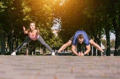 Donna adatta ed uomo di forma fisica che fanno allungando gli esercizi all'aperto al parco Immagini Stock