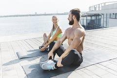 Donna adatta ed uomo di forma fisica che fanno allungando gli esercizi all'aperto alla città Fotografia Stock