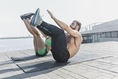 Donna adatta ed uomo di forma fisica che fanno allungando gli esercizi all'aperto alla città Fotografie Stock
