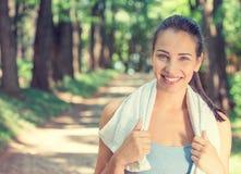 Donna adatta sorridente con l'asciugamano bianco che riposa dopo l'allenamento Fotografie Stock