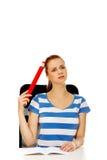 Donna adolescente che fa compito e che tiene penna enorme Fotografie Stock Libere da Diritti