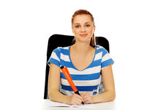 Donna adolescente che fa le note con una penna enorme Fotografie Stock Libere da Diritti