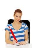 Donna adolescente che fa le note con una penna enorme Fotografie Stock