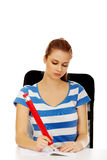Donna adolescente che fa le note con una penna enorme Immagini Stock