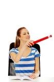 Donna adolescente che indica per qualcosa con una penna enorme Immagini Stock Libere da Diritti
