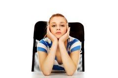 Donna adolescente stanca che si siede dietro lo scrittorio Fotografia Stock Libera da Diritti