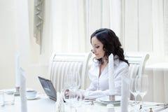 Donna adorabile che lavora al computer in ristorante fotografia stock