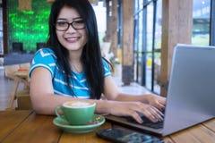 Donna adorabile che lavora con il computer portatile al caffè Immagine Stock