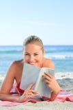 Donna adorabile che legge un libro sulla spiaggia Fotografie Stock