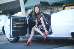 Donna adorabile che posa ed ed intorno ad un'automobile d'annata Fotografie Stock Libere da Diritti