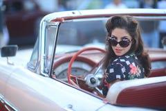 Donna adorabile che posa ed ed intorno ad un'automobile d'annata Immagini Stock