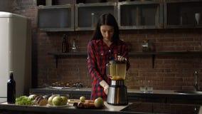 Donna adorabile che produce frullato in miscelatore in cucina video d archivio