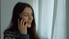 Donna adorabile che rivolge allo Smart Phone vicino alla finestra stock footage