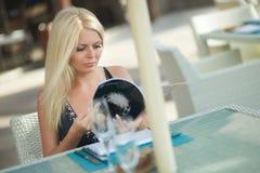 Donna adorabile e attraente che si siede nel ristorante e che legge magaz Fotografie Stock Libere da Diritti