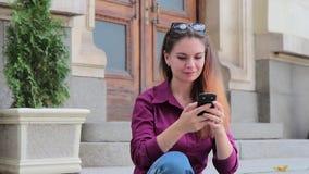 Donna adorabile fotografata su uno smartphone sulla via che si siede sulle scale archivi video