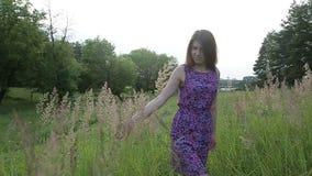Donna adorabile spensierata di salto schietta nel campo con i fiori al tramonto di estate archivi video