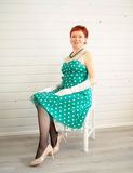 Donna adulta attraente che si siede sulla sedia Fotografia Stock Libera da Diritti