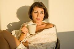 Donna adulta a casa che si siede sulla sedia davanti al caffè o al tè bevente di rilassamento della finestra fotografia stock libera da diritti