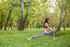 Donna adulta che allunga i muscoli delle gambe prima dell'allenamento Immagini Stock