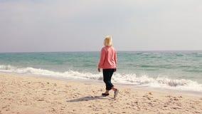 Donna adulta che cammina sulla sabbia dal mare stock footage