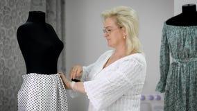 Donna adulta che crea i nuovi vestiti sul manichino nel negozio del sarto archivi video