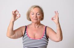 Donna adulta che fa yoga con i segni giusti della mano Fotografia Stock Libera da Diritti