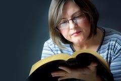 Donna adulta che legge una bibbia Fotografie Stock Libere da Diritti