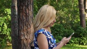 Donna adulta che osserva in telefono cellulare mentre camminando nel parco verde il giorno di estate archivi video