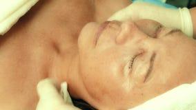 Donna adulta che ottiene una procedura cosmetica facciale in una clinica di cosmetologia stock footage