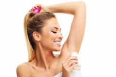 Donna adulta che per mezzo del deodorante immagini stock