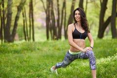 Donna adulta che si esercita nel parco mentre ascoltando la musica Fotografia Stock
