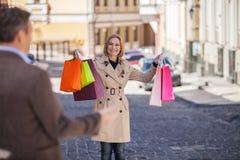 Donna adulta che tiene le borse variopinte fuori Immagini Stock Libere da Diritti