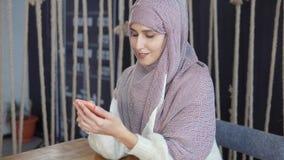 Donna adulta con hijab musulmano tradizionale sugli sms di battitura a macchina capi dal telefono cellulare archivi video